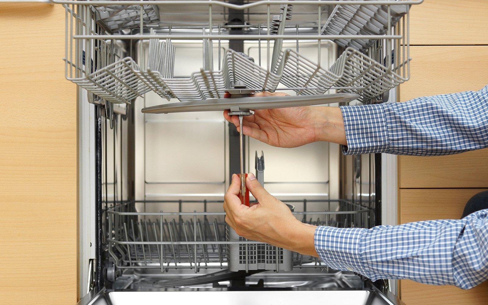 Lavoratore che ripara una lavastoviglie