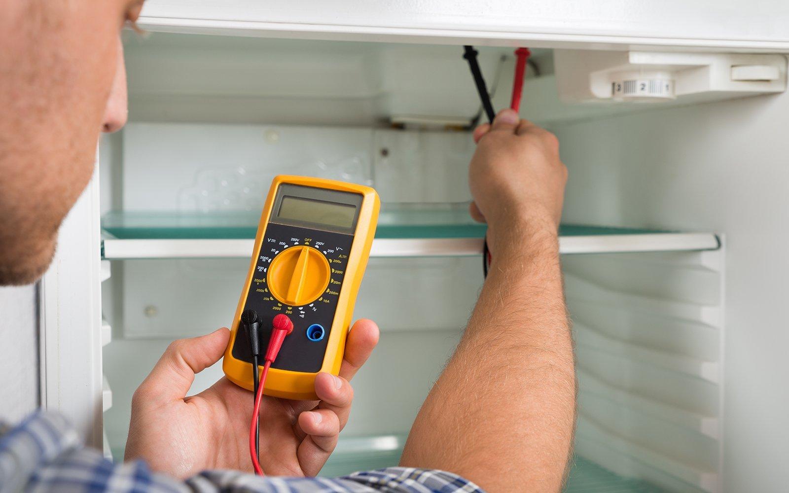 Giovane tecnico maschio che controlla frigorifero con il multimetro digitale