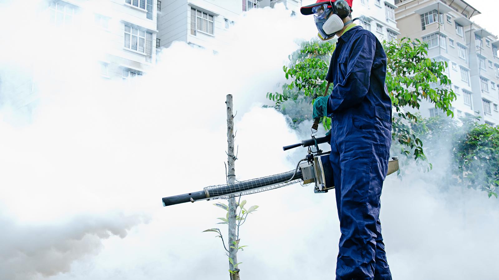 un uomo con una maschera durante una disinfestazione all'aperto