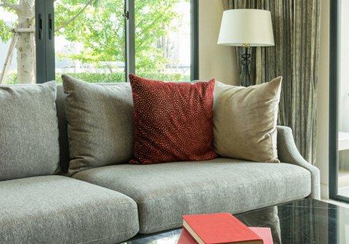 un divano grigio con tre cuscini di diversi colori