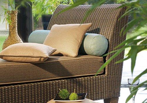 un divanetto marrone da esterno con dei cuscini