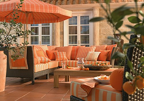 un divano da esterno con cuscini arancioni e bianchi e un ombrellone