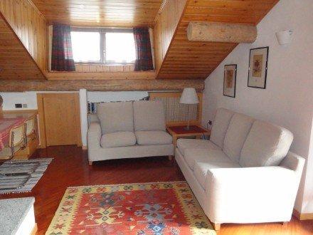 salotto con 2 poltrone bianche e tappeto colorato