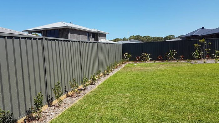 green color bond fencing with flower beds