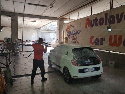 un uomo che lava una macchina con un' idropulitrice