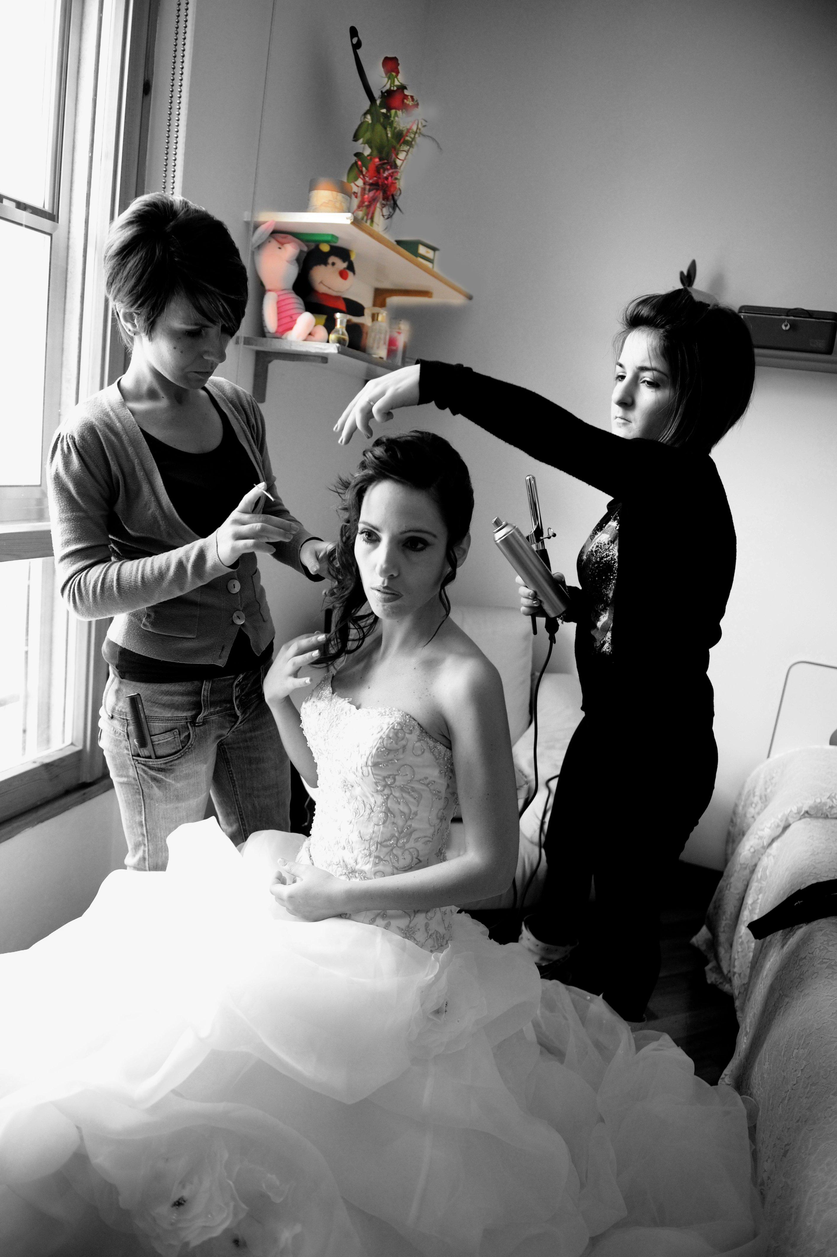 due parrucchiere che acconciano una sposa