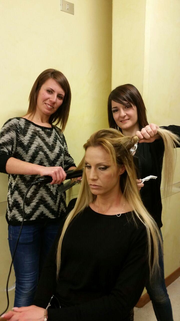 due parrucchiere che piastrano i capelli a una donna