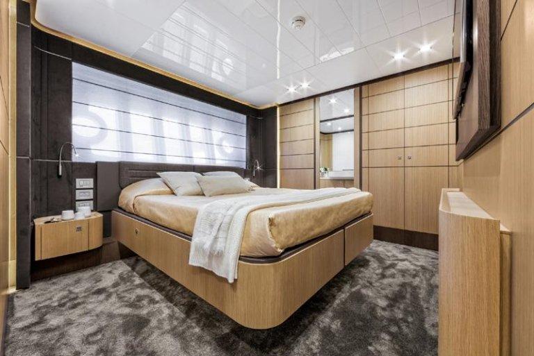 Camera da letto di legno con letto molto grande chiaro