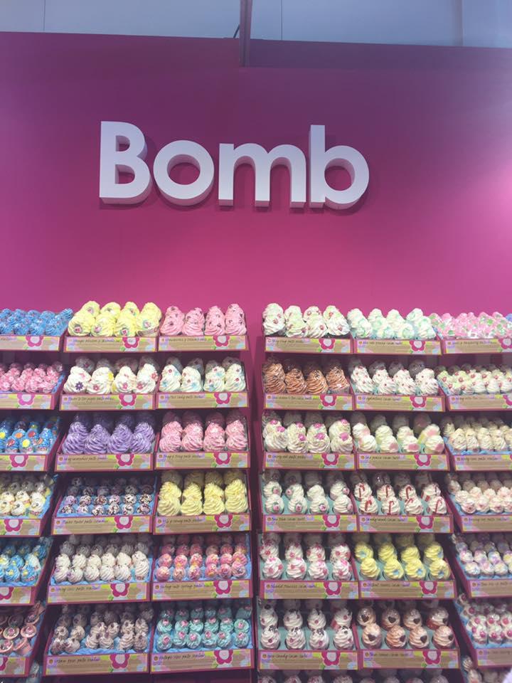 una parete viola con scritto Bomb e sotto dei prodotti di diversi colori negli scaffali