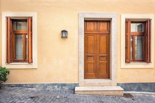 facciata di uno stabile con una porta e due finestre in legno