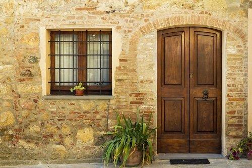 facciata di uno stabile con porta e  finestra in legno