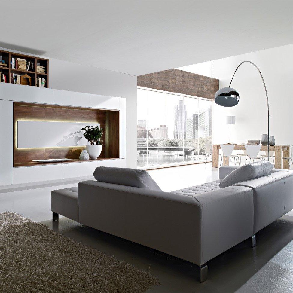 salotto con divano grigio, lampada e a destra una finestra e un tavolo