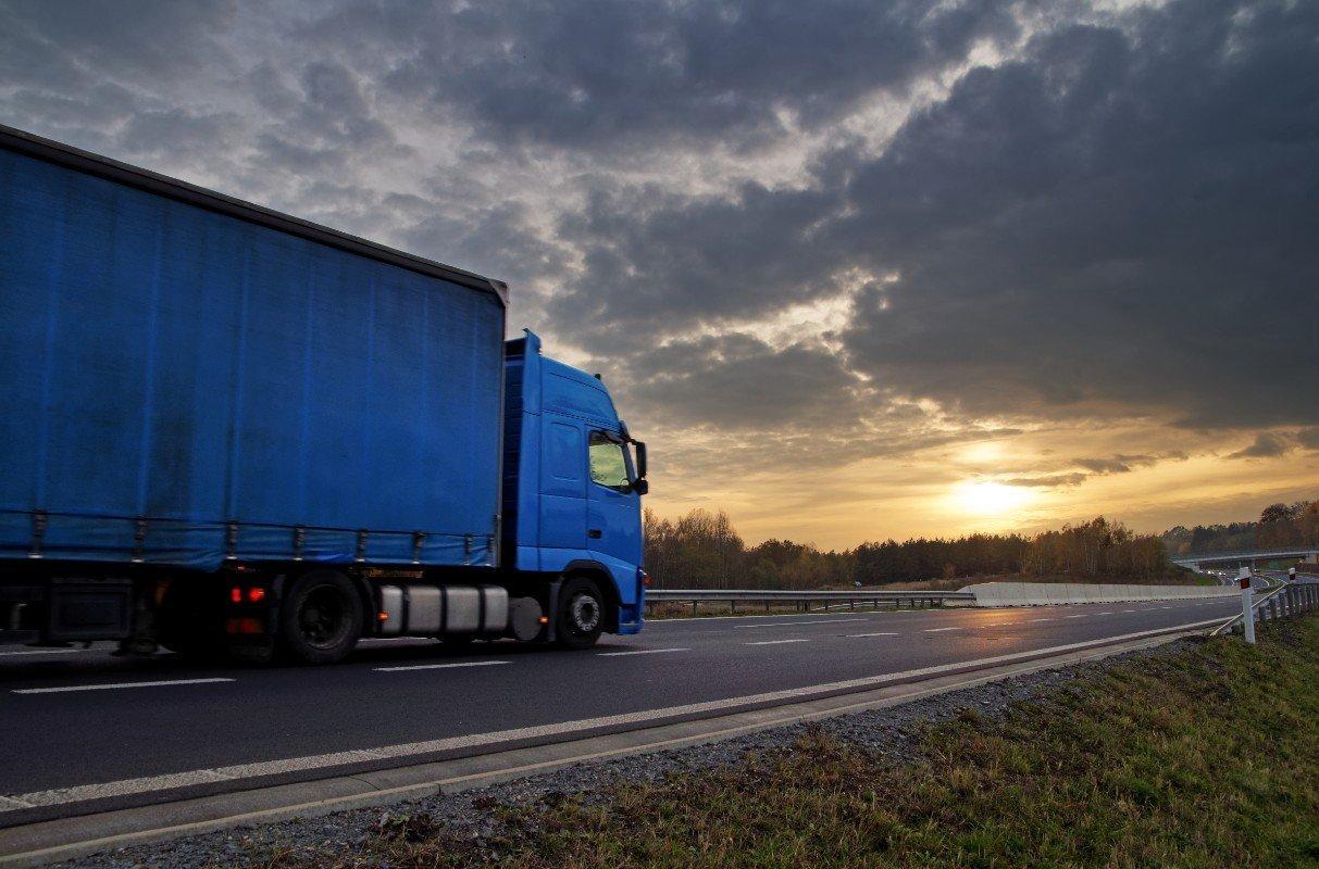 Camion blu conducendo  un'alba appannata