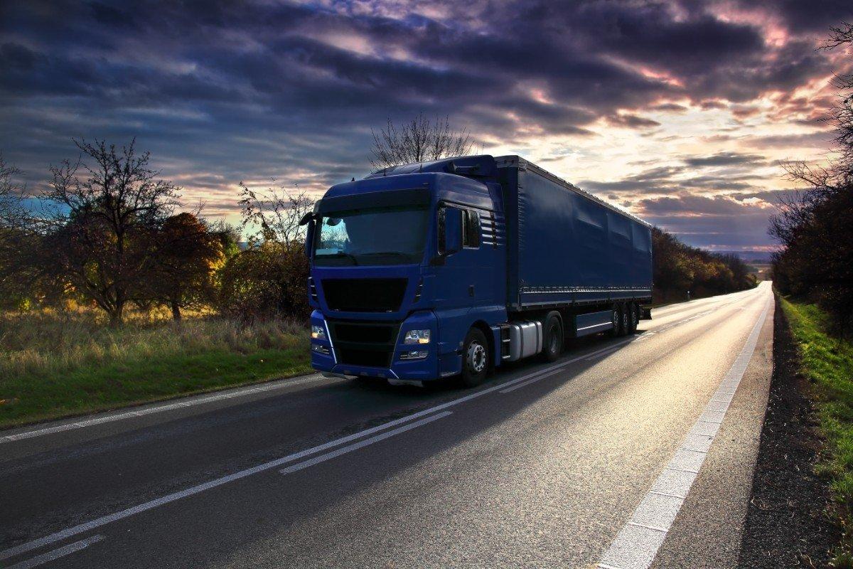 Frontale di un camion blu in un'alba tra nubi