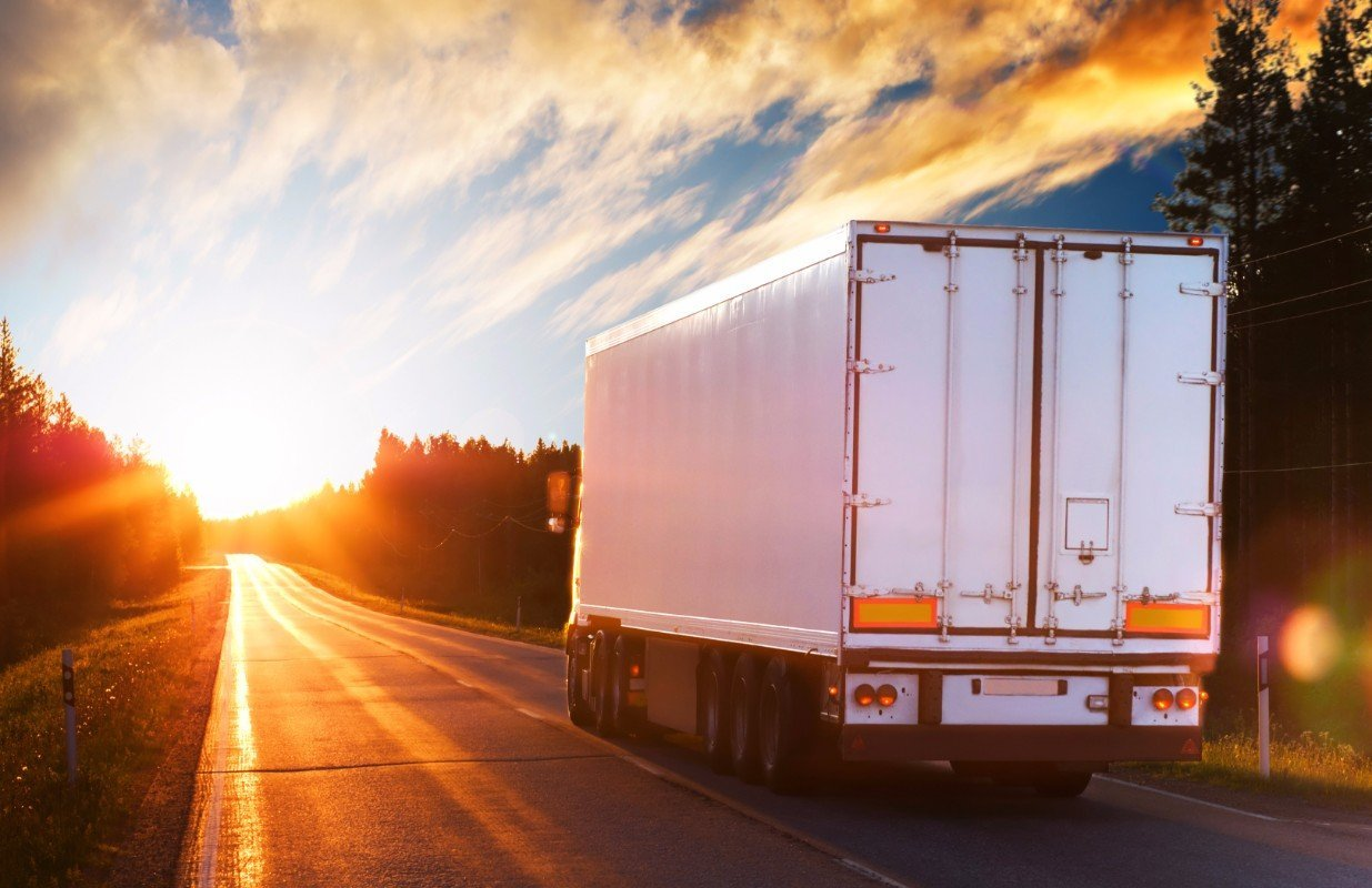 Parte posteriore di un camion bianco in rotta all'alba