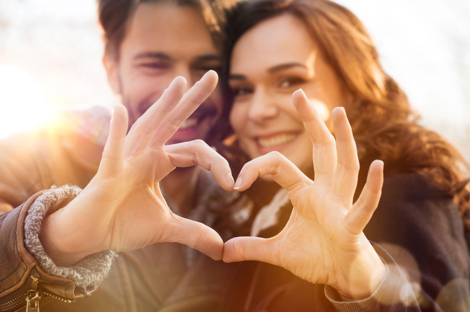 uomo e donna fanno un cuore con le loro mani