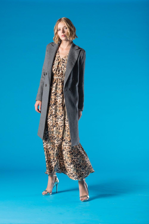 ragazza con vestito lungo a trama fantasiosa e giacca lunga