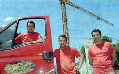 team di operai edili in posa davanti a una gru