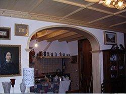 interno di una casa con un'arcata, dei mobili, quadri e soffitti in legno