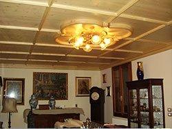 una sala con dei mobili in legno e delle cornice dorate al muro