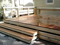 dei gradini in legno e un terrazzo rialzato di una casa