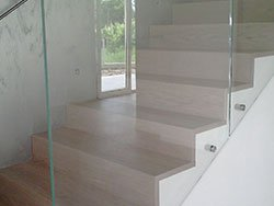 delle scale in legno con corrimano in vetro