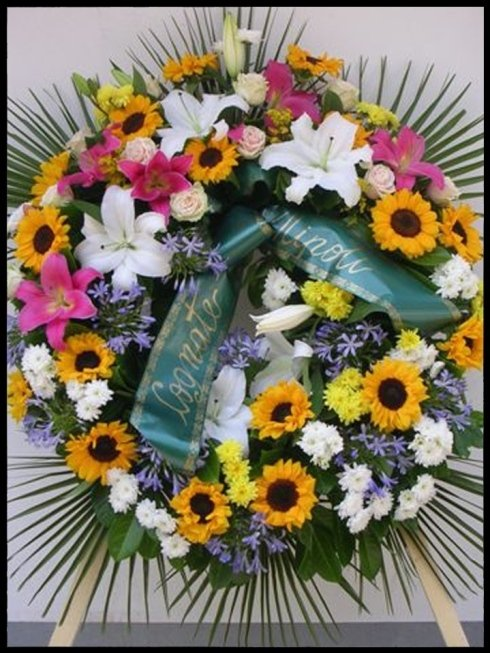 Corona funebre con girasoli, lilium, agapanto, rosa talea e crisantemo euro