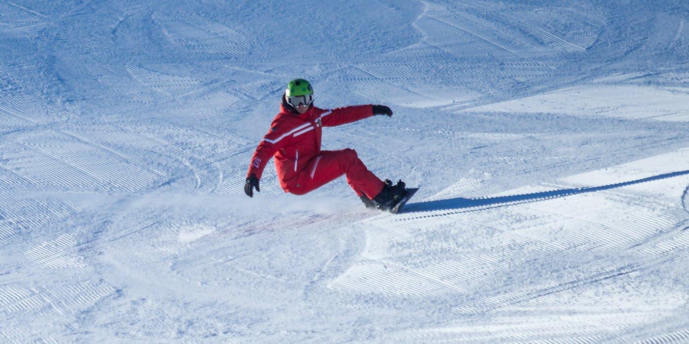 vista di un ampio spazio inneveato e di un uomo con il caschetto verde e vestito di rosso sullo snowboard