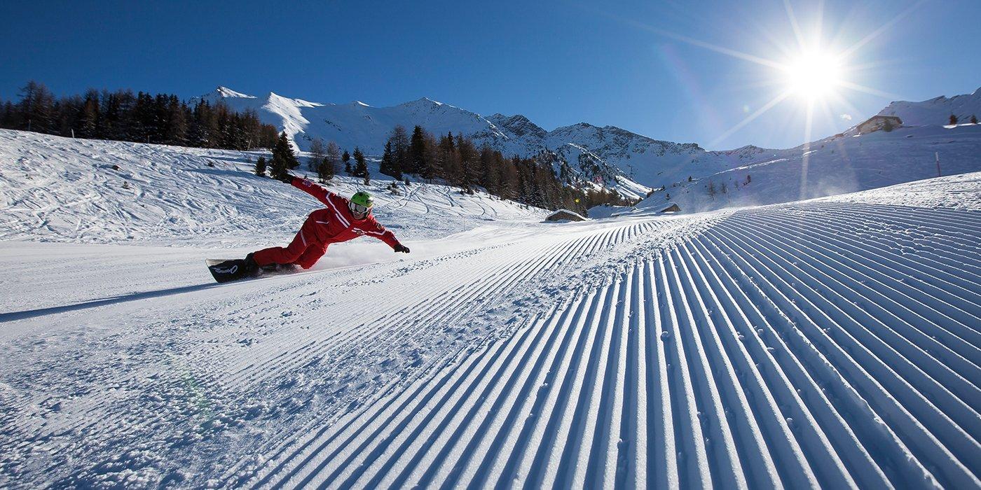 vista di una pista da sci in fondo sulla sinistra degli alberi, montagne innevate, sole acciecante e un uomo sullo snowboard