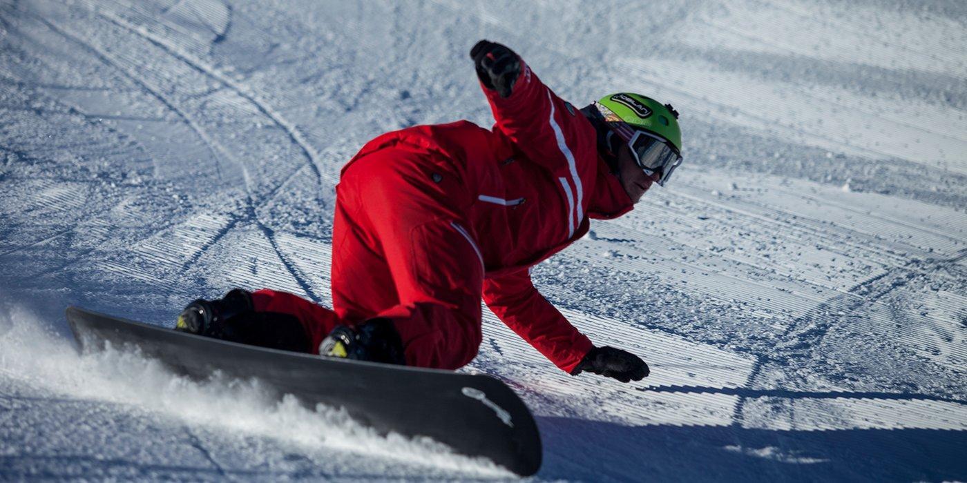 vista da vicino di un uomo vestito di rosso con un caschetto verde mentre curva sullo snowboard