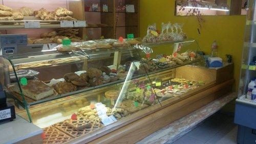 una vetrina con delle crostate al cioccolato, focaccia e altro