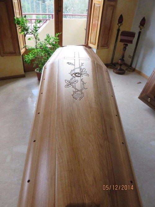 Una bara in legno con il simbolo della croce e dei fiori
