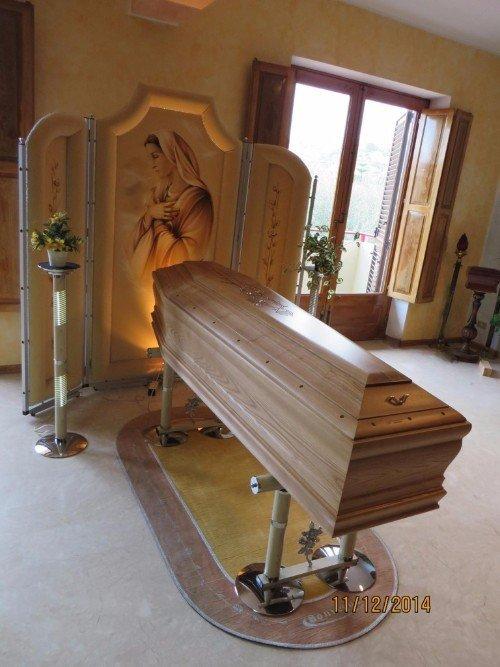 Una bara in legno chiaro e un pannello con il volto della Madonna disegnato