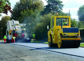 A steam roller leveling out a newly laid road surface