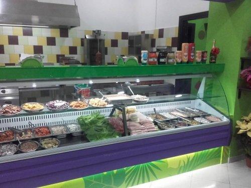 una vetrina con dell'insalata, piadine e altri piatti pronti