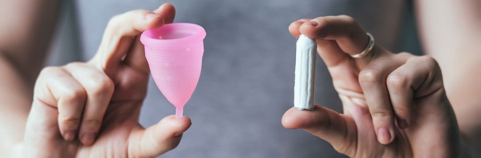 Woman hands holding pink menstrual cup and OB - female hygiene products
