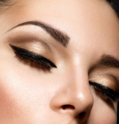 A lady with closed eyelids, showing pale gold shadow and black liner