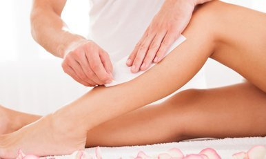 A lady having her legs waxed with strips