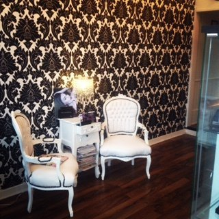 A small white chest of drawers and two white Queen Anne chairs in front of a flock-papered wall