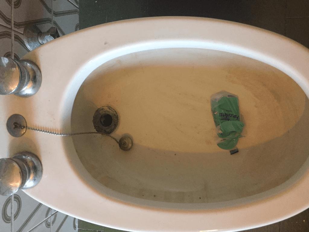 un bidet sporco con dentro una bottiglia