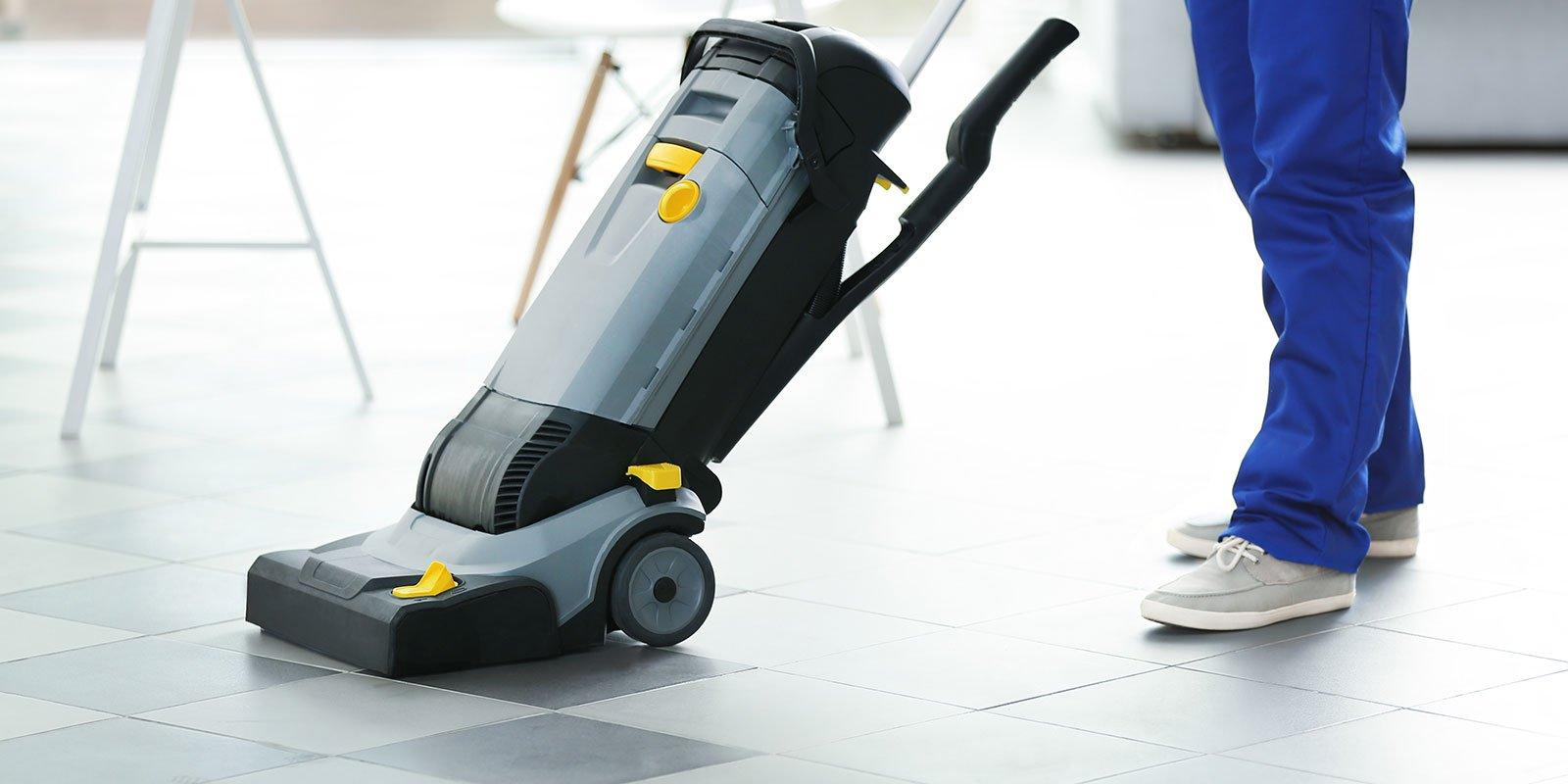 Giovane bidello con pavimento pulizia lavatrice in ufficio