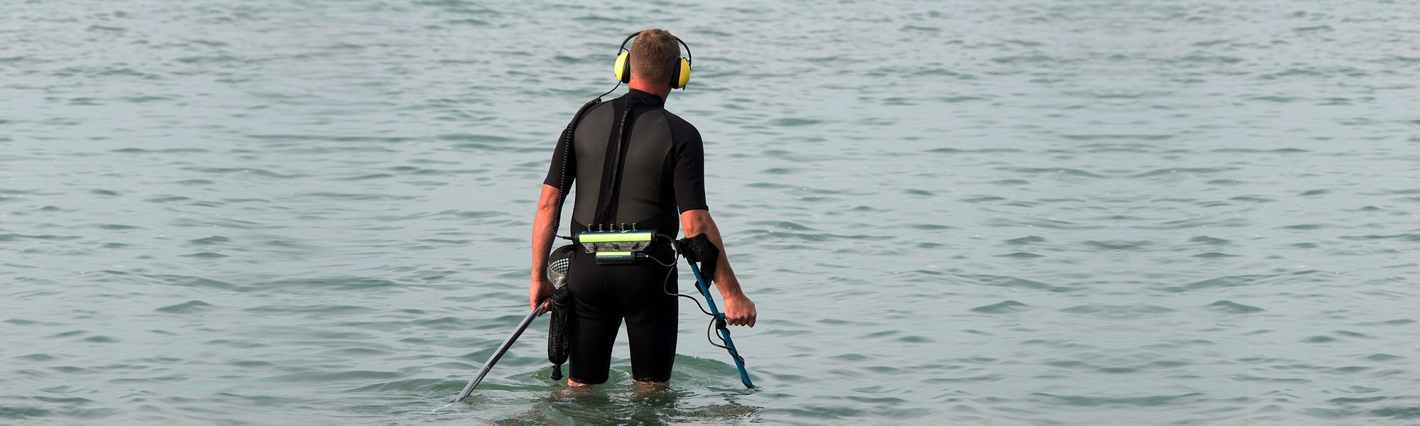 Man in the water with metal detector