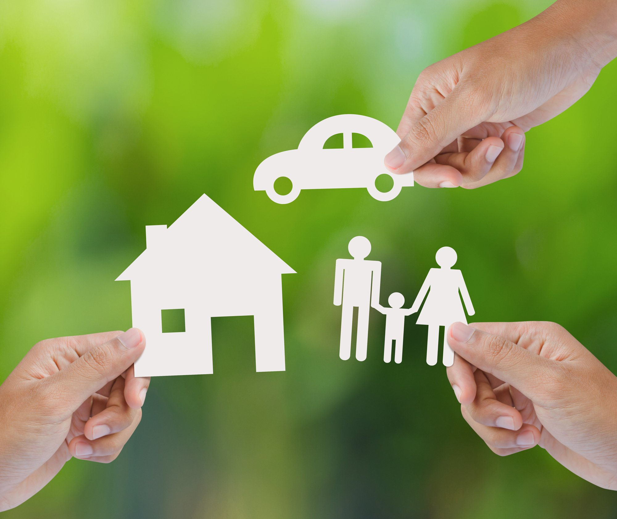 Conceptual image with hands holding paper cutouts of a house, family and car