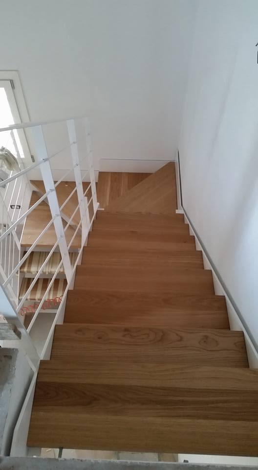 Una scala curva in legno con corrimano in ferro dipinto di bianco