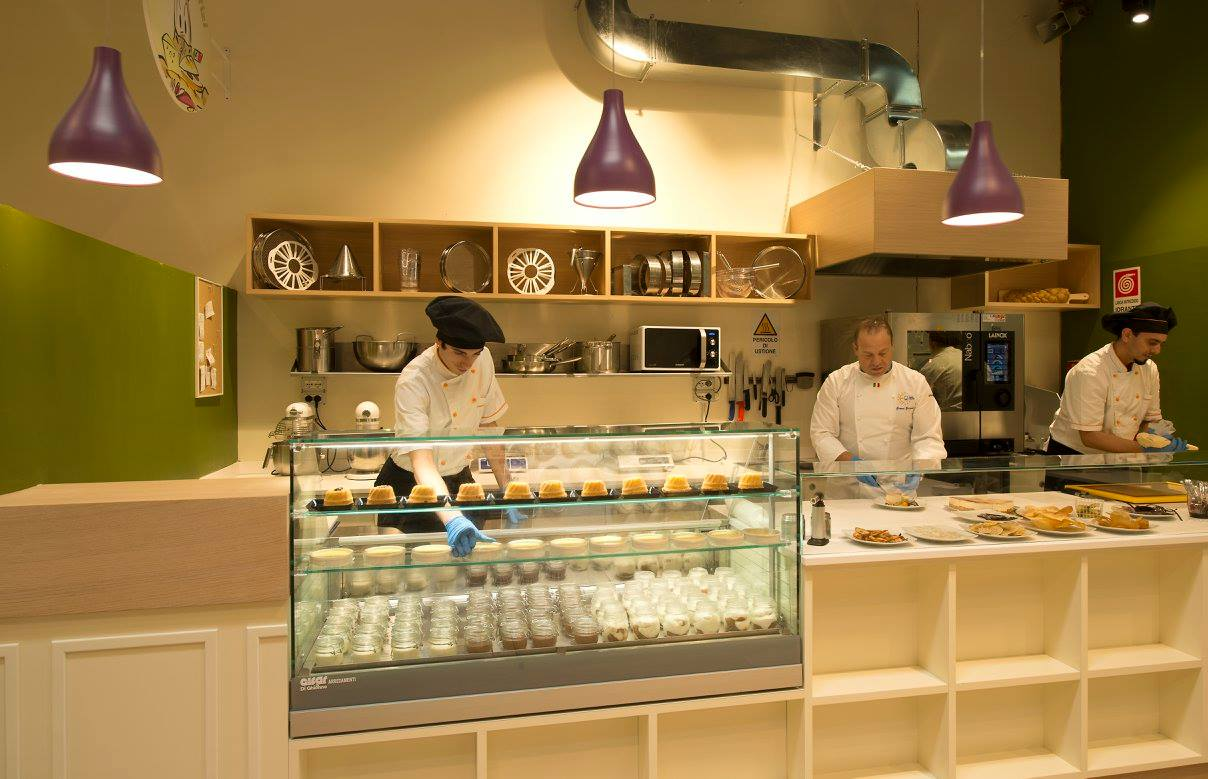 All'interno di un ristorante con la cucina e bancone di color bianco e tre membri del personale dietro al  bancone mentre impiattano e organizzano una vetrina