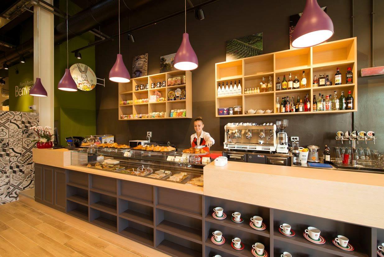 All'interno di un bar, bancone di color legno chiaro, mensole di color grigio dietro il bancone una barista mentre prende una tortina da una tortiera