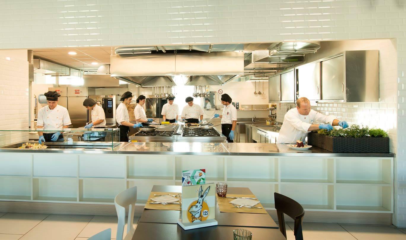 All'interno di una cucina professionale del ristorante con sette membri del  personale che cucinano e un altro cuoco mentre raccoglie degli aromi dalle piantine appoggiate sull'angolo del bancone