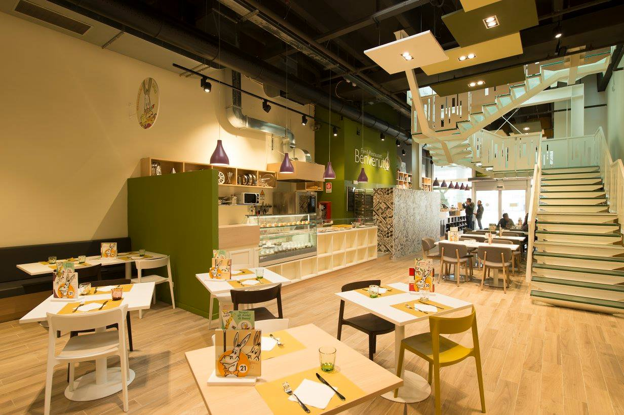 All'interno di un ristorante vista dei  tavoli da due con sedie di color verde, nero e bianco, bancone con vetrina sulla sinistra e sulla destra delle scale con corrimano di color bianco