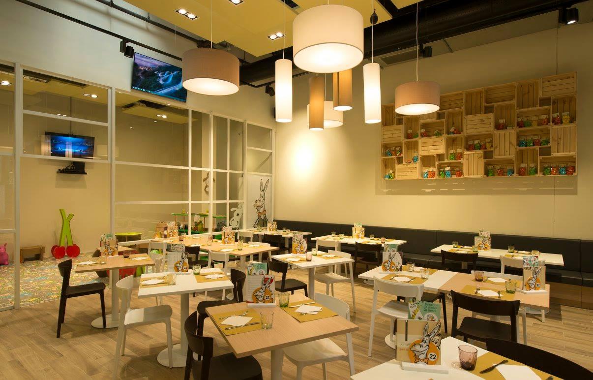 Interno di un ristorante con le lampade a sospensione, un monitor al muro, tavoli beige chiari, bianchi e sedie di color bianco e nero