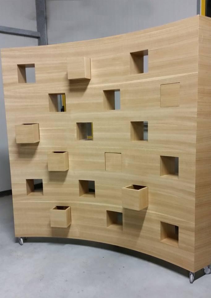 Un pannello curvo in legno chiaro con delle finestrelle incavate e vasi di legno a forma quadrata